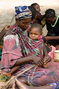 Local woman with child crafting handicraft goods. Namibia.