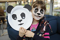 Child with panda face paint and panda mask from LPC official opening event.