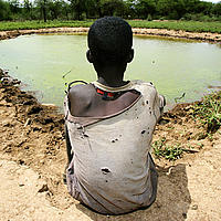 A boy sits on the ground while overlooking a dam built by his village. Lake Bogoria, Kenya
