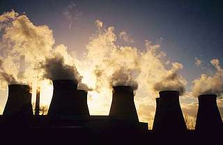 Cooling towers letting out steam and smoke at a coal-fired power station near Pontefract in Yorkshire, UK.