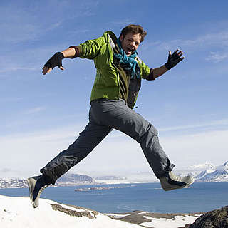UK Ambassador for Change, Casper ter Kuile, jumping over rocks in Spitsbergen, Norway