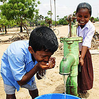 Children using a newly built water pump in the village of Karikkattukuppam in India, Asia