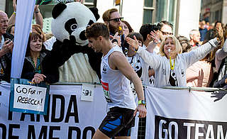 A Team Panda London Marathon runner high fives cheering supporters