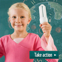 Girl holds low energy lightbulb in front of chalkboard - 'Take Action'.