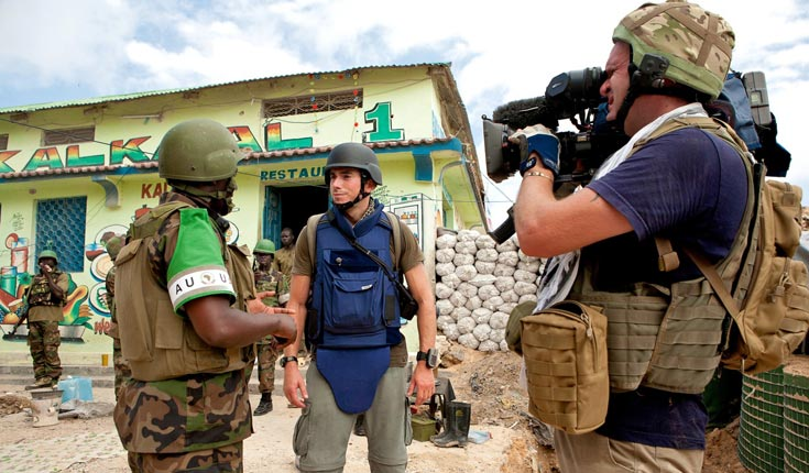 Jonathan Young, cameraman (right) and Simon Reeve (centre), with Ugandan peacekeeping troops on the frontline in Mogadishu, Somalia © Andrew Carter
