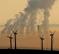 Steam rises from a power station behind a wind farm