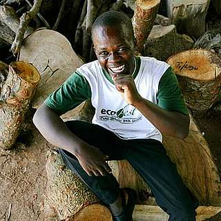 Alex Kubi sitting amongst a pile of FSC coded logs, Akamba Handicrafts, Kenya