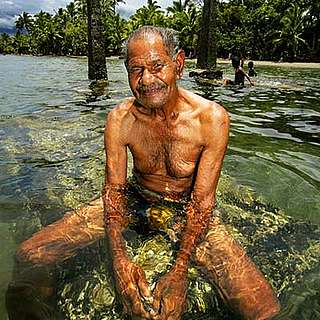 Local man at his family burial site, now submerged in water, Navua, Fiji