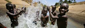 A group of boys play in the irrigation channel that runs through Rweja town, Tanzania.