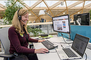 Staff member using jabber telephone headset in open plan office areas of the the new headquarters building of WWF-UK, the Living Planet Centre, Woking, Surrey© WWF-Canon / Richard Stonehouse