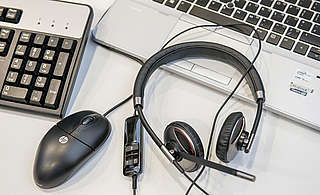 Jabber phone headset with volume adjustment, placed on a laptop